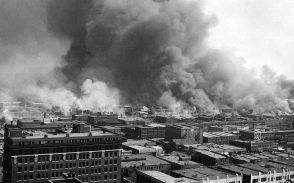 Tulsa's Greenwood district, the wealthiest black neighborhood in the nation, in flames during the 1921 riot. Image via Wikimedia Commons.